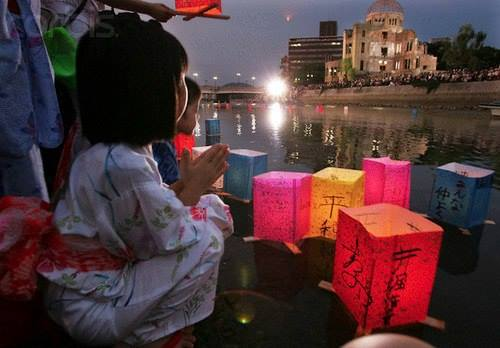 Behind her the dome ruins in Hiroshima.Japanese children in summer kimono offer prayers with paper lanterns..jpg